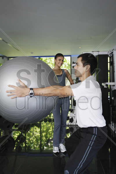 man exercising with fitness ball, woman watching stock photo