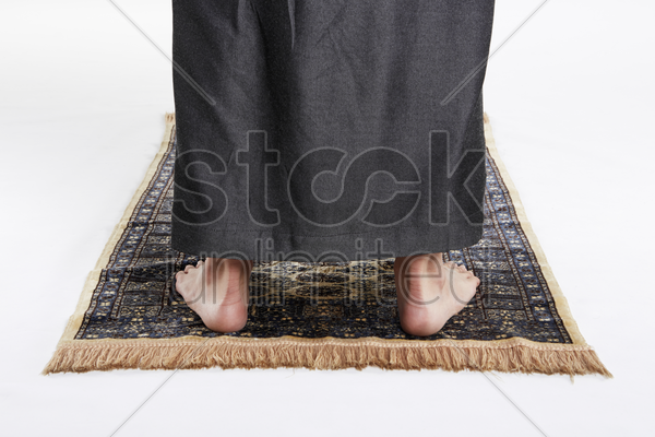 man facing the qiblah with the intention of performing prayer stock photo