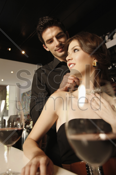 man fastening woman's necklace stock photo