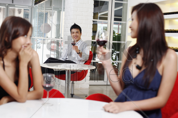 man flirting with woman sitting at another table stock photo