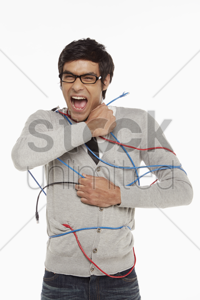 man freeing himself from tangled network cables stock photo