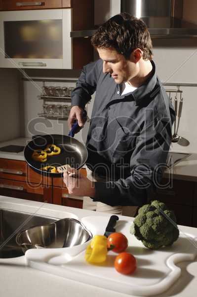 man frying capsicum in the kitchen stock photo
