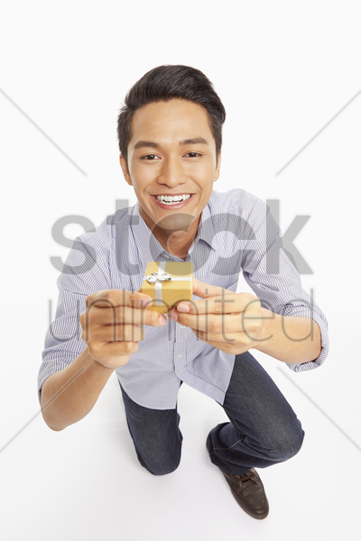 man getting down on one knee to propose stock photo