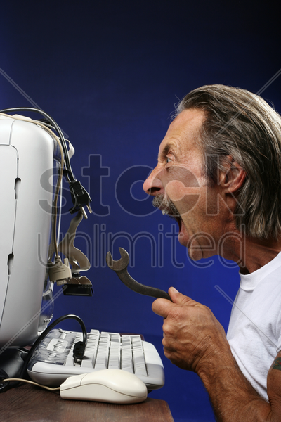man getting frustrated while fixing his computer stock photo