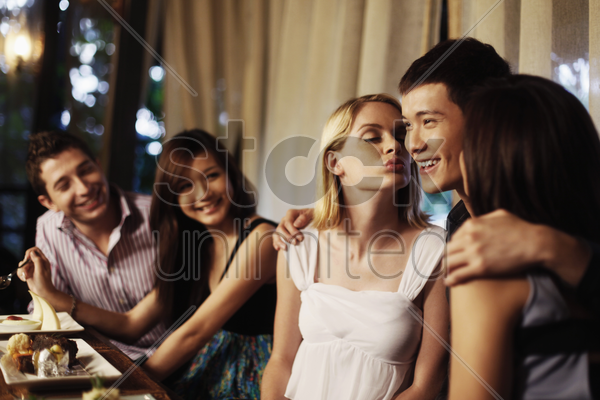 man getting kisses from two women, friends watching stock photo