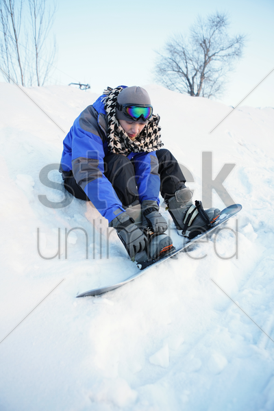 man getting ready for snowboarding stock photo
