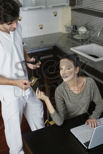 man giving credit card to woman for online shopping stock photo