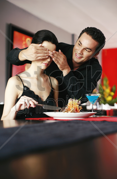man giving his girlfriend a surprise stock photo