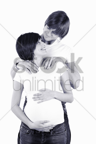 man giving his pregnant wife a shoulder massage stock photo