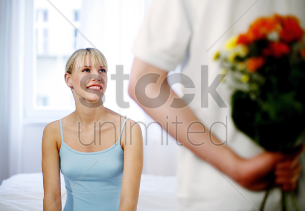 man giving his wife a bouquet of flowers stock photo