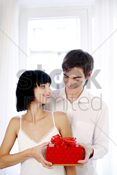 man giving his wife a surprise gift stock photo