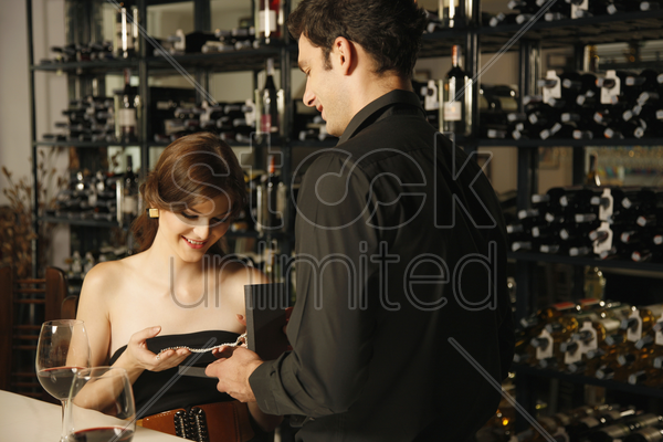 man giving woman a diamond necklace stock photo