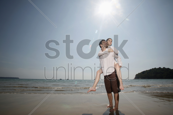 man giving woman a piggy back ride on beach stock photo