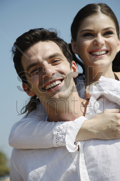 man giving woman a piggy back ride stock photo