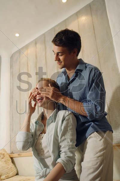 man giving woman a surprise by covering her eyes stock photo