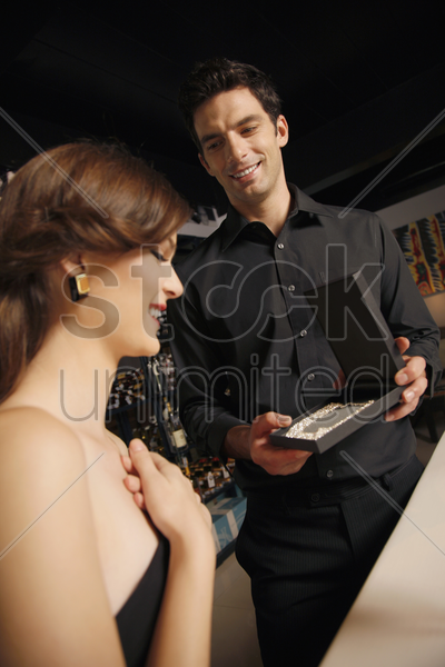 man giving woman a surprise gift stock photo