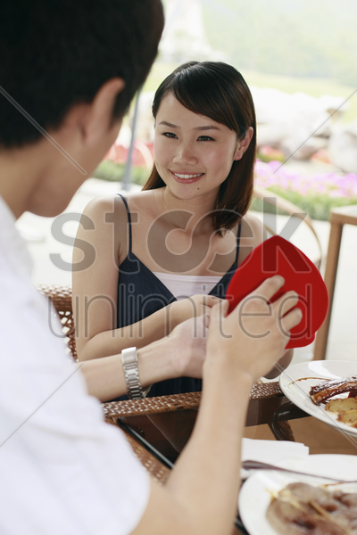 man giving woman a surprise present stock photo