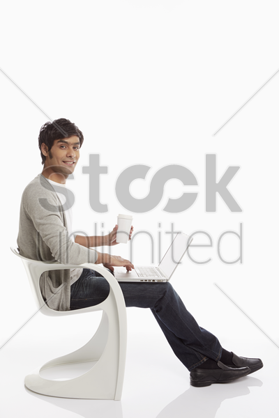 man having a drink while using laptop stock photo
