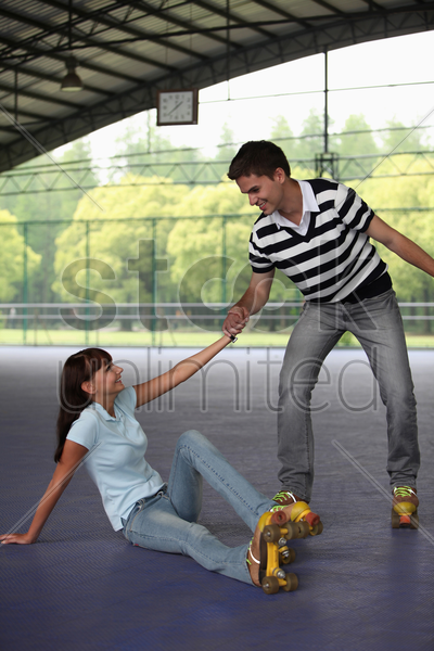 man helping woman up stock photo