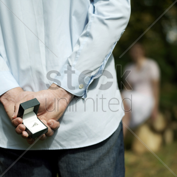 man hiding a ring from his girlfriend stock photo