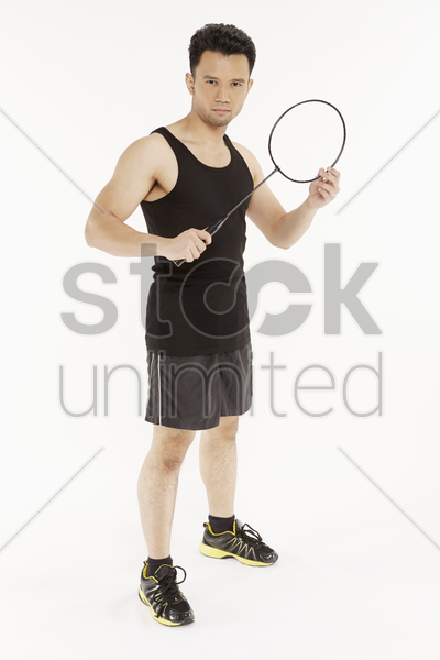 man holding a badminton racket stock photo