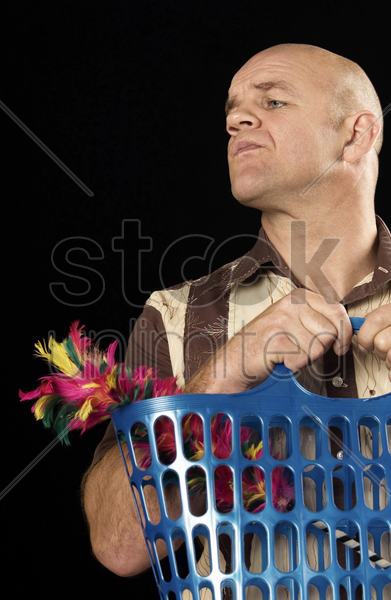 man holding a basket with a feather duster in it stock photo