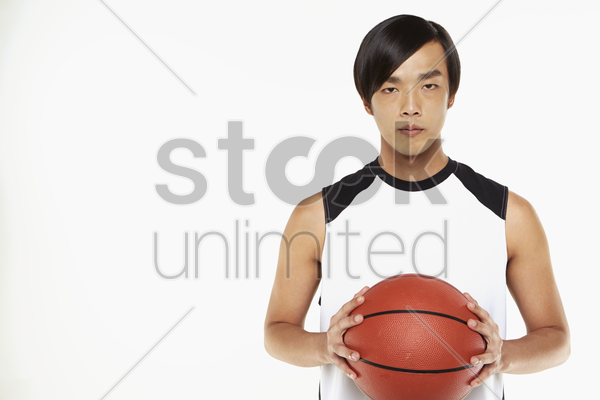 man holding a basketball stock photo