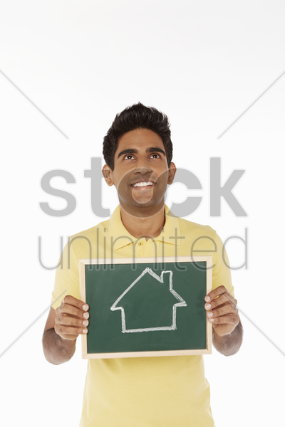 man holding a blackboard with a house doodle on it stock photo