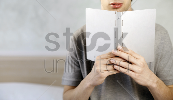 man holding a book stock photo