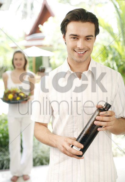 man holding a bottle of drink with his girlfriend holding a basket of flowers stock photo