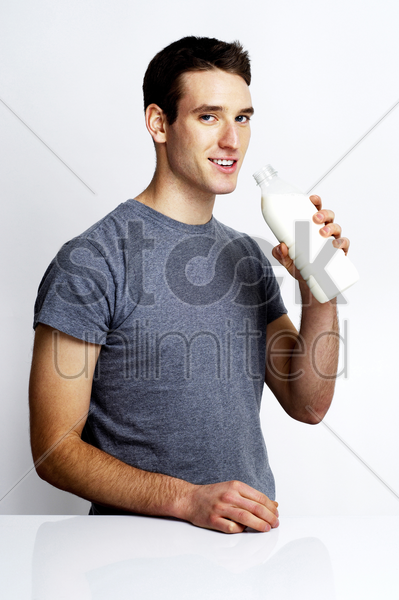 man holding a bottle of milk stock photo