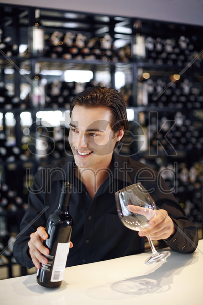man holding a bottle of wine and a wine glass stock photo
