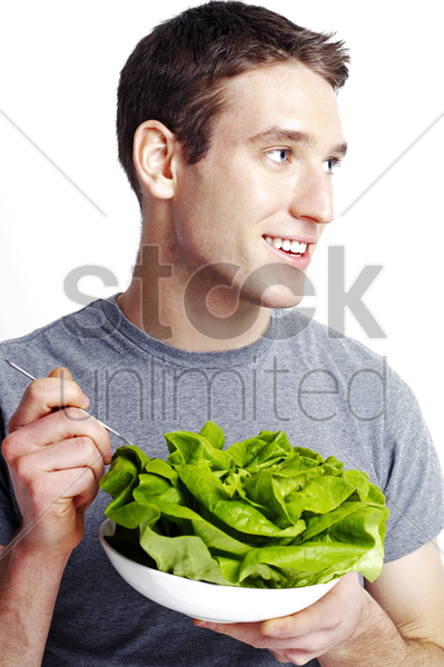 man holding a bowl of salad stock photo