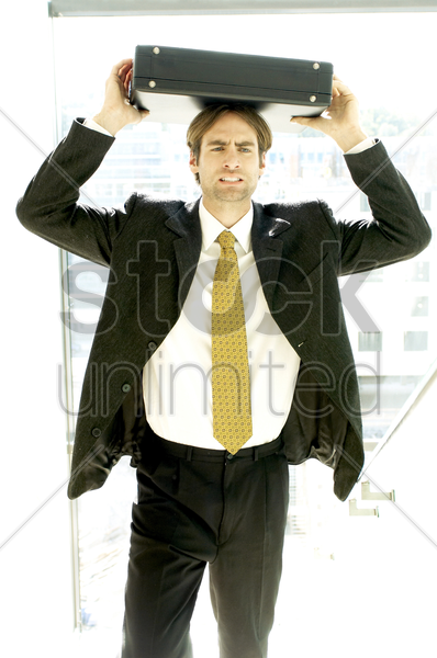 man holding a briefcase on his head stock photo