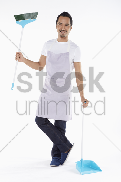 man holding a broom and dustpan stock photo