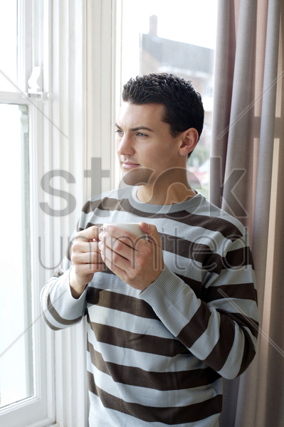 man holding a cup of coffee while enjoying the view from the window stock photo