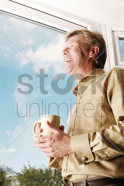 man holding a cup while looking out of the window stock photo