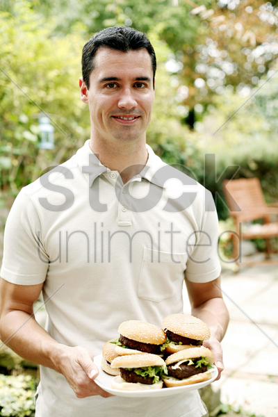 man holding a plate of burgers stock photo