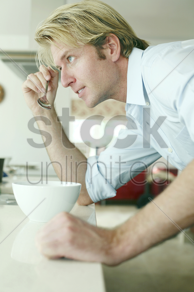 man holding a spoon with a bowl in front of him stock photo