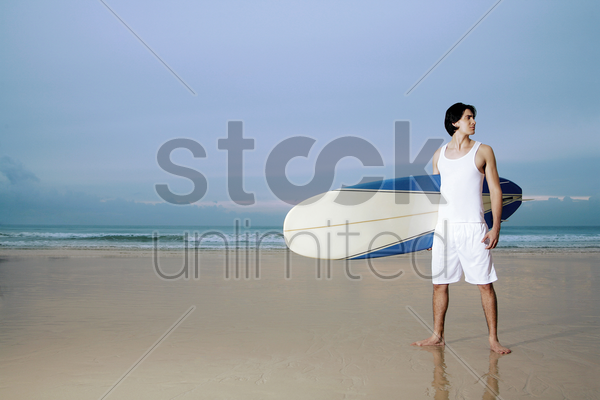 man holding a surfboard stock photo