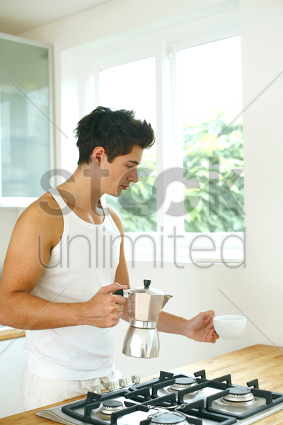 man holding a teapot and a teacup stock photo