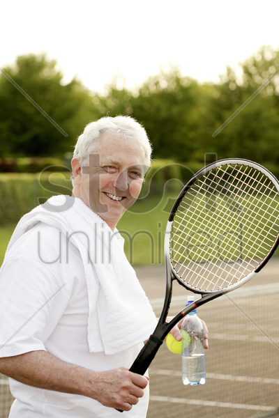 man holding a tennis racquet and a bottle of water stock photo
