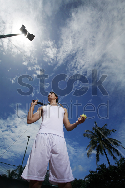 man holding a tennis racquet and tennis ball stock photo