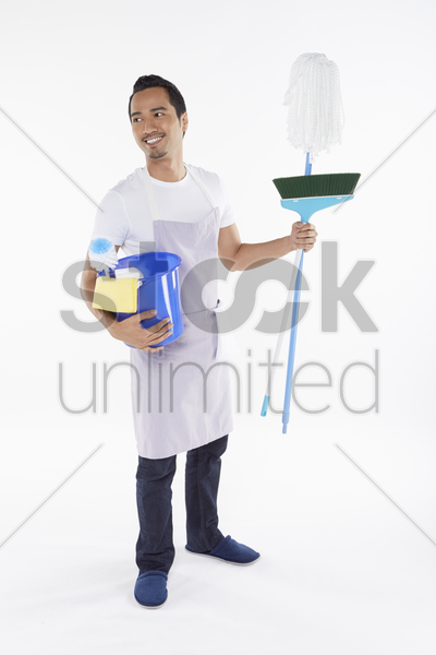 man holding a variety of cleaning supplies stock photo