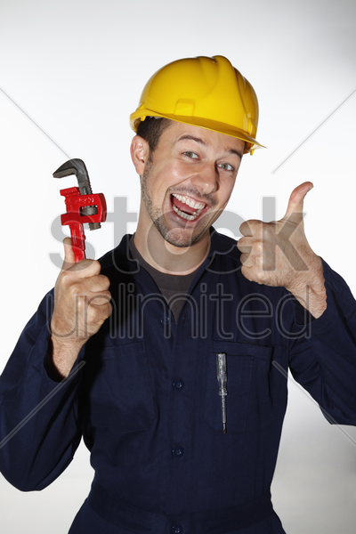 man holding adjustable wrench and showing thumbs up stock photo