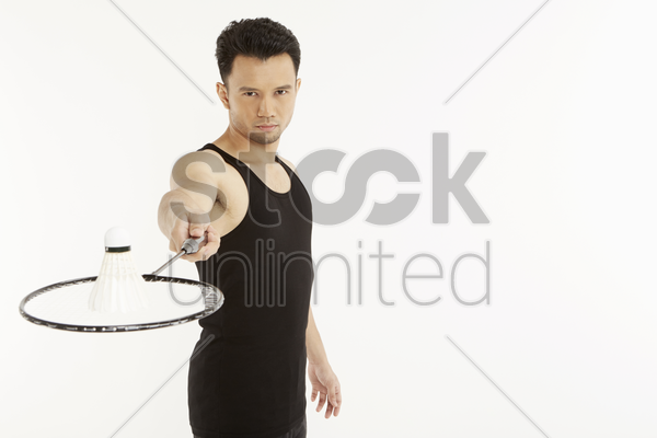 man holding badminton racket with a shuttlecock placed on it stock photo