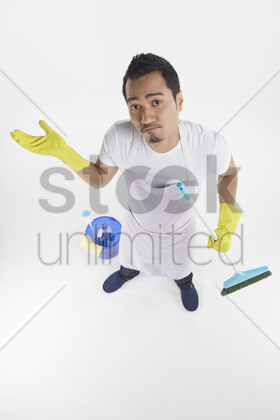 man holding cleaning supplies stock photo