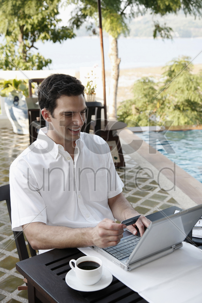 man holding credit card while using laptop stock photo
