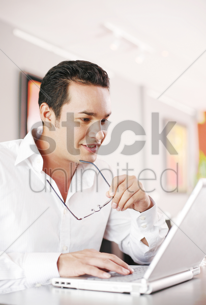 man holding his glasses while using laptop stock photo