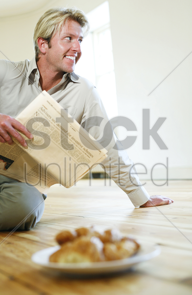 man holding newspaper with a plate of croissants on the floor stock photo